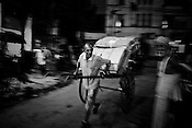 A rickshaw puller is seen pushing the rickshaw with packaging cardboards in Calcutta, India. 93 out of every 100 rickshaw pullers are homeless. They sleep after the city sleeps and wake up before everyone else does. Many of them are the sole bread earners for their family. Many plus 40. Many minus any other specialisation for any other job. Of the twenty four thousand rickshaw pullers, only 387 have licenses. .Many rickshaw pullers earn a meagre wage of 100-150 rupees (US $ 2.25-3.5) a day of which they have to give a daily rickshaw rent of 60 (US$ 1.35) rupees to the agent at the end of the day.