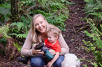 A local Caucasian woman, a young part-Asian boy and their dog pause along the native forest loop trail at Kalopa State Park, Hamakua Coast, Big Island.