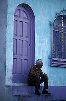 Grey-haired man sitting on the steps of a restored house in Flores, an island town in Lake Peten Itza, El Peten, Guatemala