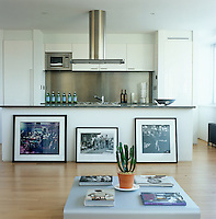 Large photographic prints lean against the marble-topped island which divides the living space from the kitchen