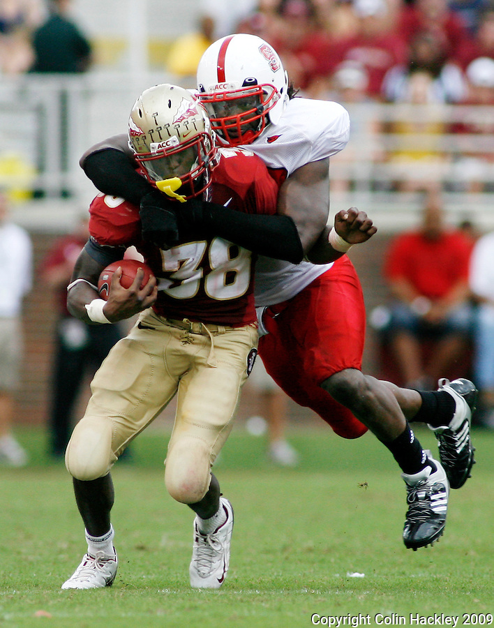 TALLAHASSEE, FL 10/31/09-FSU-NCST FB09 CH36-Florida State's Jermaine Thomas is dragged down by N.C. State's Willie Young after a 22-yard run during first half action Saturday at Doak Campbell Stadium in Tallahassee. .COLIN HACKLEY PHOTO