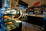 A worker prepares a case of pastries in a cafe in the Spaccanapoli shopping district of Naples.