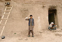 A young Hazara with a pigeon and here mother spinning woollen in here house next to the giant Buddha of Bamiyan.