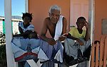 A family on the porch of their house in Camp Corail, a controversial resettlement of earthquake survivors north of Port-au-Prince, Haiti. Thousands of families were relocated to Corail from flood-prone areas of the capital in 2010, yet the promises of jobs that lured them there failed to materialize.