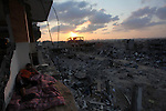 A Palestinian man lies down among a destroyed house after returning home in the Tufah neighbourhood in eastern Gaza City on August 31, 2014. Calm returned to the coastal enclave in a August 26 ceasefire, and Gazans were gradually starting to rebuild their lives after a bloody and destructive 50-day war, the deadliest for years. Photo by Ashraf Amra