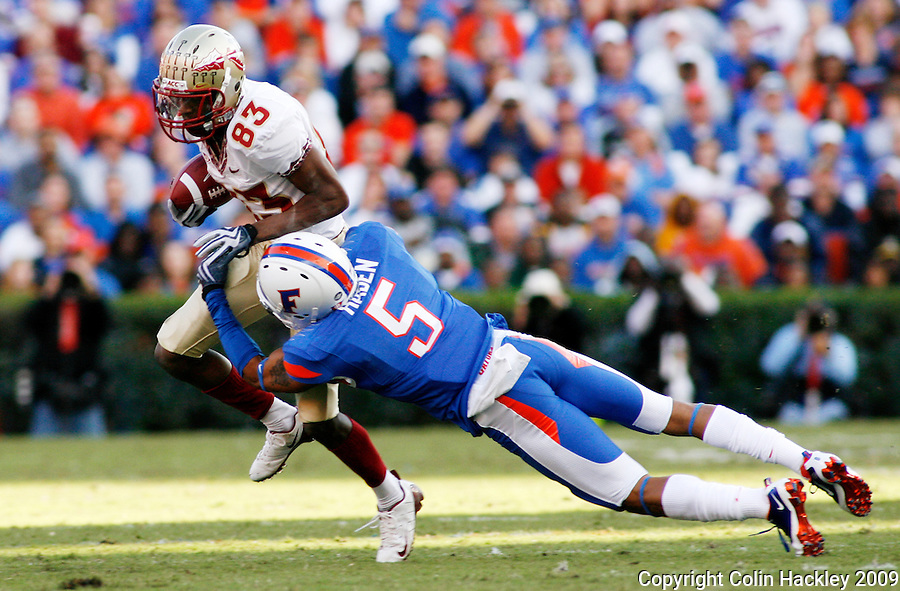 GAINESVILLE, FL 11/28/09-FSU-UF FB09 CH06-Florida State's Bert Reed is tackled by Florida's Joe Haden during first half action Saturday at Florida Field in Gainesville. .COLIN HACKLEY PHOTO