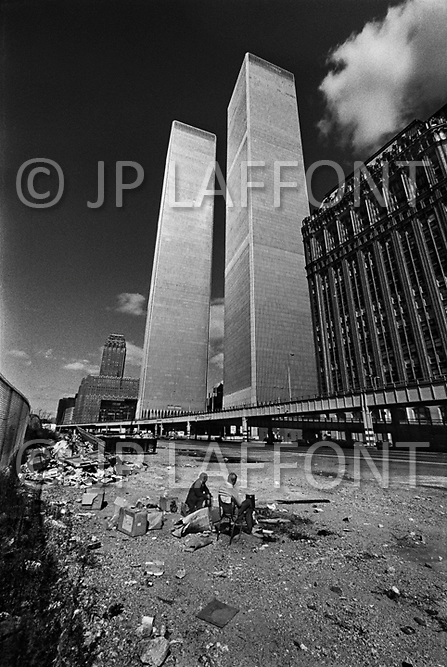 Manhattan, New York City, NY. October, 1975. <br /> Two homeless men squat below the recently constructed World Trade Center. New York was bankrupt, in shambles and the building was not occupied.