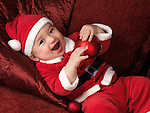 Happy smiling six month old baby boy in Santa Christmas costume lying on a sofa with a red bauble in his hands