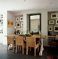 The formal dining room is in neutral tones. There is a use of natural materials seen in the wooden table, the cane chairs and the slate floor