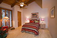 Guest bedroom shown with window shutters and wood beamed tonhue in groove ceiling