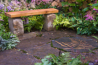 Beautiful garden bench in spring garden with Astilbe, cut firewood logs, Brunnera, Arisaema, decorated patio