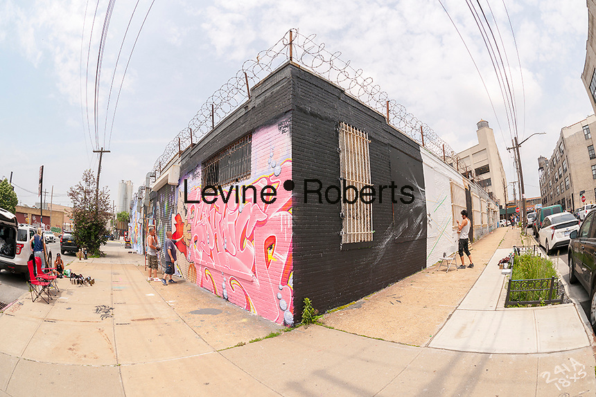 "Artists work on murals in Bushwick, Brooklyn in New York during the annual Bushwick Collective Block Party on Saturday, June 4, 2016. Music and partying brought some but the real attraction was the new murals  by ""graffiti"" artists that decorate the walls of the buildings that the collective uses.  (© Richard B. Levine)"