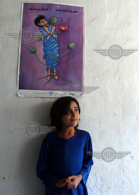 A girl in the Nejat Drug Treatment Centre, beneath a poster of a man strangled by poppies, emphasising the danger of opium addiction.
