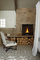 The fireplace surrounded by a limestone wall is a feature of the master bedroom