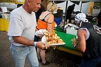 People eat at vendor's tents at the Testicle Festival at the Rock Creek Lodge in Clinton, MT. The Rock Creek Lodge in Clinton, MT, has hosted the annual Testicle Festival since the early 1980s.  The four day festival and party revolves around the consumption of so-called Rocky Mountain Oysters, which are deep-fried bull testicles.