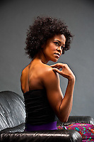 Young African American woman sitting on sofa looking over shoulder