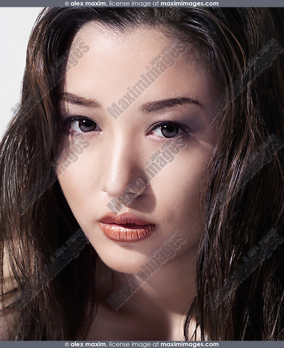 Young asian woman beautiful sexual face with long wet dark hair and big brown eyes closeup beauty portrait