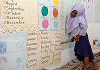 Jambiani, Zanzibar, Tanzania.  African Muslim Schoolgirl Points to the Arabic Name of the Days of the Week.  Students learn Arabic so they can read the Koran.  English is the language of higher education and the courts in Tanzania.  Swahili is the mother-tongue on Zanzibar.