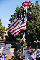 "Vicky waves a flag with a sign saying ""bank owned"" at the top of it during the activities at the Occupy Orange County, Irvine camp on November 5."