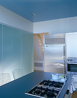A wall of frosted glass, a cool blue and white colour-scheme and the minimum of clutter have resulted in a kitchen of tranquil simplicity