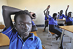 A boy raises his hand during class in a school in the Southern Sudanese village of Kenyi. The school was constructed by the United Methodist Committee on Relief (UMCOR).  Families here are rebuilding their lives after returning from refuge in Uganda in 2006 following the 2005 Comprehensive Peace Agreement between the north and south.