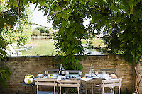 A table on the terrace with the remains of a lazy summer lunch