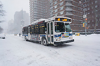 An MTA bus equipped with chains for traction travels down Ninth Avenue in the New York neighborhood of Chelsea during Winter Storm Jonas on Saturday, January 23, 2016. Due to blizzard conditions approaching the MTA announced they will be suspending all bus service starting at noon. Subways are continuing to run. (© Richard B. Levine)