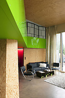A feature of the double-height open plan living area is the eye-catching lime green lacquered panelling