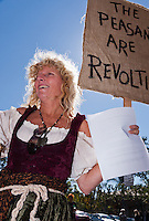 """A woman with blond curly hair holds a sign saying """"The peasants are reviling"""" at the Occupy Orange County, Irvine march on November 5."""