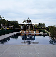 Sun-loungers at the far end of a tranquil swimming pool with an hexagonal conservatory beyond