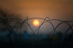 The sun sets behind barb wire inside a United Nations base in Malakal, South Sudan. More than 20,000 civilians have lived inside the base since shortly after the country's civil war broke out in December, 2013, and renewed fighting in 2015 drove an additional 5,000 people into the relative safety of the camp.