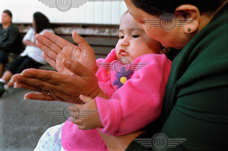 Baby Arahia Tepurei learning how to clap her hands with her grandmother during a Maori family gathering (known as a 'hui') at their home marae (tribal meeting place).