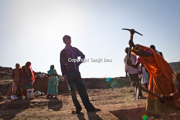 A maith (contractor) checks the work of women who work at a site as part of NREGA at Nazir ka Mandir in Karauli district of Rajasthan, India. The National Rural Employment Guarantee Act (NREGA) that has created a source of additional income for families living below the poverty line by providing a minimum 100 days of employment assured under the Act. Photo by Sanjit Das