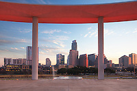 Downtown Austin, Texas, rises into the February morning. Seen here from the Long Center pavillion as the sun makes its way across the high rises, the skyline is a pleasant scene as it rests on the banks of Lady Bird Lake. Just across the street is Zilker Park, as well.