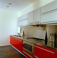 A bank of red kitchen units with a thick stainless steel worktop occupies one wall beyond the open-plan dining area