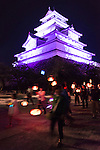 People carry lanterns in front of Tsuruga-jo castle during the Aizu Festival in Aizuwakamatsu City, Fukushima Prefecture, Japan.  Photographer: Rob Gilhooly