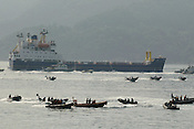 SURROUNDED BY JAPANESE POLICE AND COAST GUARD GREENPEACE INFLATABLES &quot;PROTEST&quot; ( bear witness...) IN UCHIURA BAY, BESIDE THE TAKAHAMA NUCEAR PLANT, AS BNFL SHIP 'PACIFIC PINTAIL' DEPARTS LATE AFTERNOON AFTER COLLECTING REJECTED PLUTONIUM MOX FUEL, FOR SHIPMENT BACK TO THE UNITED KINGDOM. TAKAHAMA, JAPAN. 04/07/02. .PIC &copy; JEREMY SUTTON-HIBBERT/GREENPEACE 2002..*****ALL RIGHTS RESERVED. RIGHTS FOR ONWARD TRANSMISSION OF ANY IMAGE OR FILE IS NOT GRANTED OR IMPLIED. CHANGING COPYRIGHT INFORMATION IS ILLEGAL AS SPECIFIED IN THE COPYRIGHT, DESIGN AND PATENTS ACT 1988. THE ARTIST HAS ASSERTED HIS MORAL RIGHTS. *******