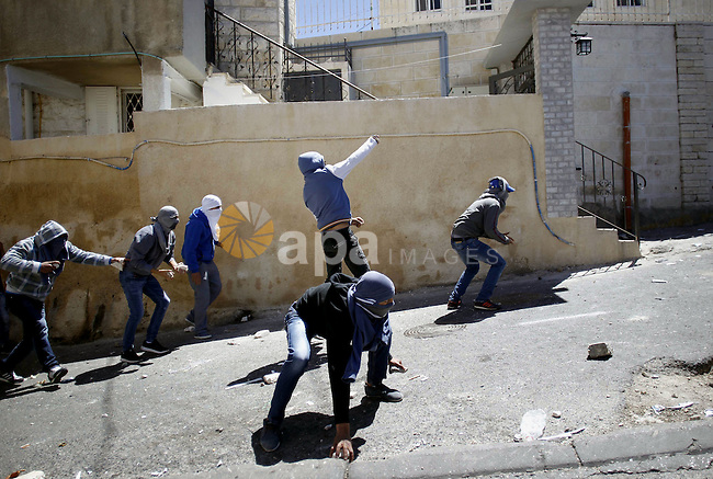 A masked Palestinian youths throw stones towards Israeli security forces during clashes on April 25, 2015 in Al-Tur neighbourhood of annexed Arab east Jerusalem, after Israeli police shot dead a knife-wielding Palestinian who attempted to stab colleagues at an east Jerusalem checkpoint. The 17-year-old assailant from Al-Tur managed to get past one checkpoint but was brought down at a second near Al-Zaim without any police casualties, a spokeswoman said. Photo by Saeb Awad