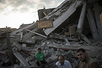 "In this Friday, Aug. 15, 2014 photo, Palestinian men sit at the rubble of a house building destroyed by an israeli airstrike during the ""Protective Edge"" military operation in Shuyaja neighborhood in Gaza City. After a five days truce was declared on 13th August between Hamas and Israel, civilian population went back to what remains from their houses and goods in Gaza Strip. (Photo/Narciso Contreras)"