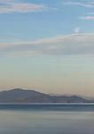 The nearly-full moon is seen above a hazy Flathead Lake, Montana near sunset.