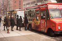 Customers line up at the Stouffer's Mac n' Cheese food truck outside the World Financial Center in Lower Manhattan in New York on Tuesday, February 5, 2013. The truck, a re-branded Eddie's Pizza Truck, has been covered in Stouffer's decor and is serving macaroni and cheese from different locations daily, with celebrity chefs creating their own mac n' cheese concoctions on several days. The truck will be around until February 14 with all profits going to the Mayor's Fund to Advance New York City's hurricane sandy relief efforts.  (© Richard B. Levine)