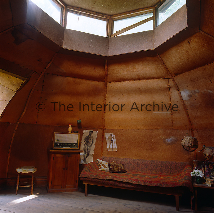 A rustic living room lined in wood panels is situated in the domed roofspace of this Russian dacha