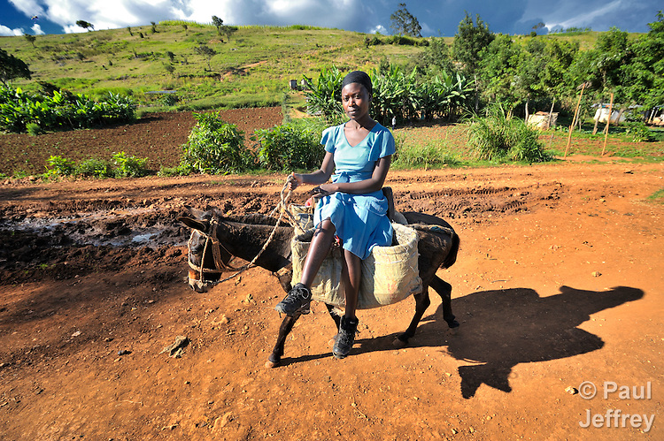 In the Haitian village of Foret des Pins, a woman rides a donkey.