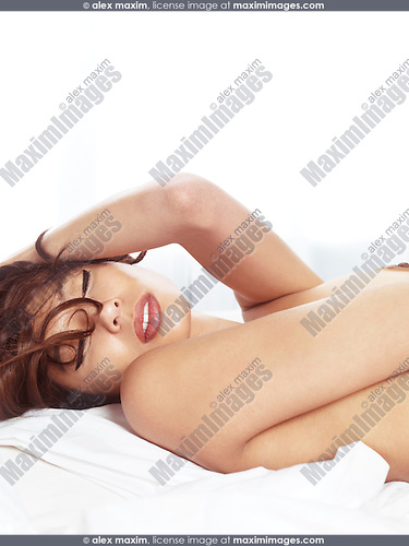 Sensual portrait of a beautiful young woman lying topless in bed