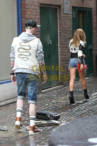 Kylie Minogue shoots a her new pop video in central London, England..April 19th, 2012.full length film filming black boots leather jacket white red heart print jacket denim jean cut offs shorts sunglasses shades  back behind rear walking gesture drop dropping .CAP/HIL.©John Hillcoat/Capital Pictures .