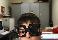 Joe Ortega (cq), the school nurse, checks the eyes of 6 year-old Cristobal Nevares (cq) at Brown Elementary School in Denver.  The Denver Public Schools Pupil Assistnce Fund provides winter coats, clothing vouchers, eye exams and glasses for the 62% of Denver Public Schools' students who qualify for the free and reduced lunch progam. Joe Ortega has been working at Brown Elementary for over 19 years as the school nurse. .(JAVIER MANZANO / THE ROCKY MOUNTAIN NEWS).Joe Ortega (cq) Cristobal Nevares (cq)