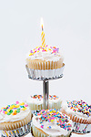 Cupcake stand with lit candle at top celebrating a special event