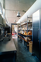 The functional stainless steel kitchen is concealed from the main living area of the loft behind a concrete partition
