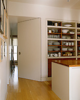 Crockery and glassware is displayed on open shelves in this contemporary kitchen