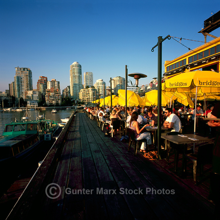 People dining outdoors at Bridges Restaurant on Granville Island at False Creek, Vancouver, British Columbia, Canada, in Summer